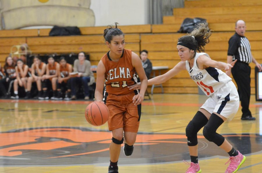 Number 21, Audrey Gonzalez, pushes past a defender towards the basket. Photo by Tori Valdez