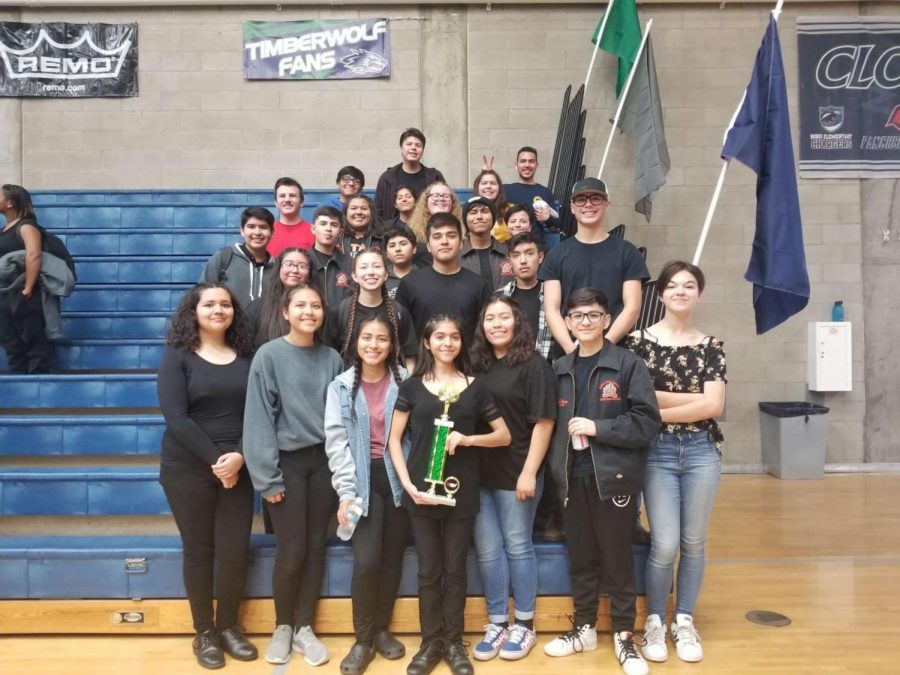 The winter percussion ensemble poses for a picture after receiving an award at one of their competitions.