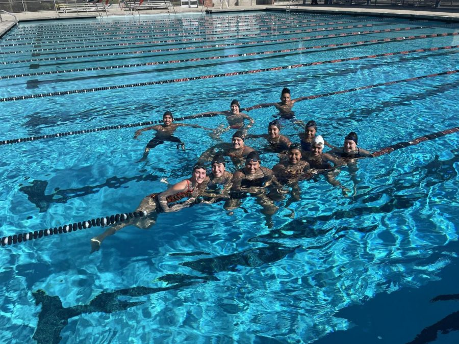 Team poses for a photo in the pool.